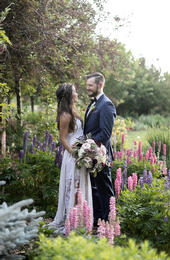 Bride and groom looking at each other while standing near flowers